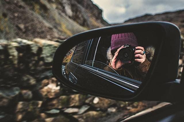 旅行中に自分のアイデンティティに悩むカメラを構えた女性の画像
