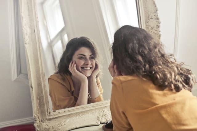 鏡に映る自分に笑いかけている女性の画像