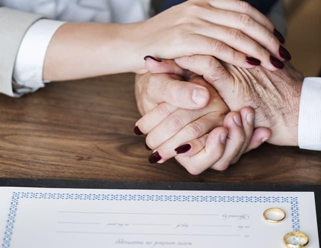 結婚指輪を並べながら婚姻届を書く夫婦の握る手の画像