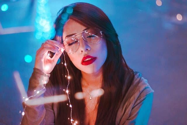 銀縁のメガネを外して優等生をやめようとする女性の画像