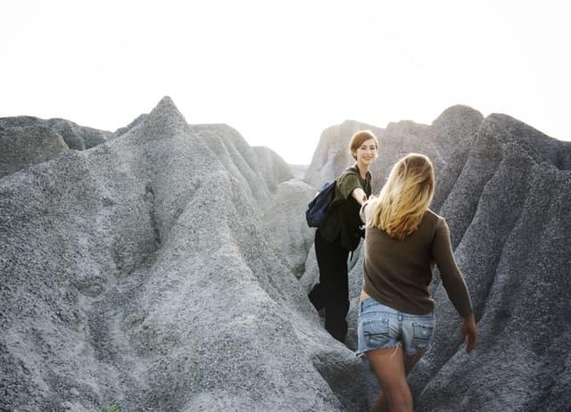 歩きづらい岩肌を友達の手を引いて助けながら歩く女性の画像