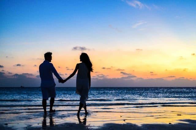 新婚旅行で砂浜を歩くカップルの画像