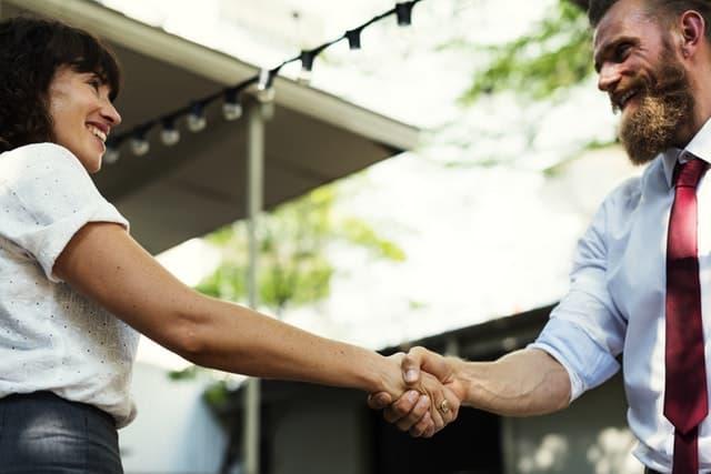 ダンディなイケオジと握手する女性の画像