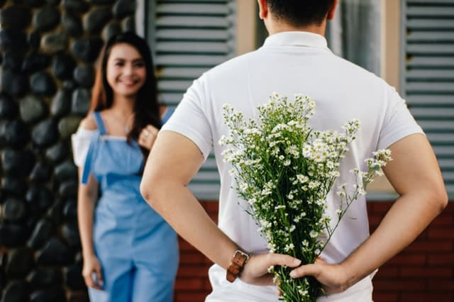 彼女へのプレゼントである花束を後ろに隠し持っている男性の画像