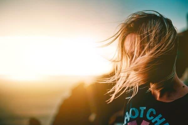 夕焼けの逆光のなかたたずむ髪で顔が隠れている女性の画像