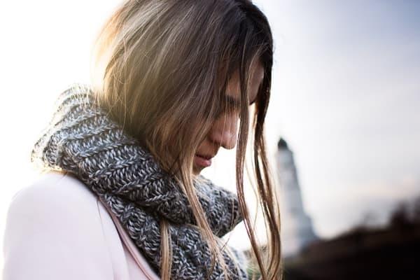 片思いに悩んでうつむいているマフラーを巻いた女性の画像
