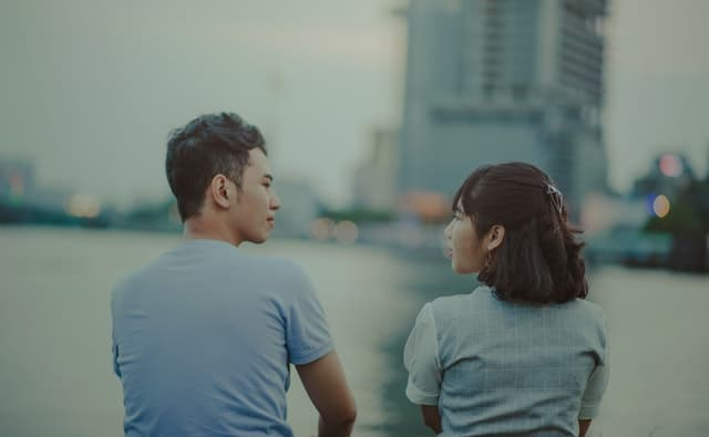 川を見ながらお互いの気持ちを探り合っている男女の画像