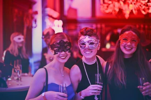 ピンク色の照明の仮面パーティで談笑する女性たちの画像