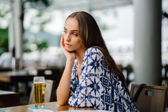 サシ飲みに飽きて無表情になっている女性の画像