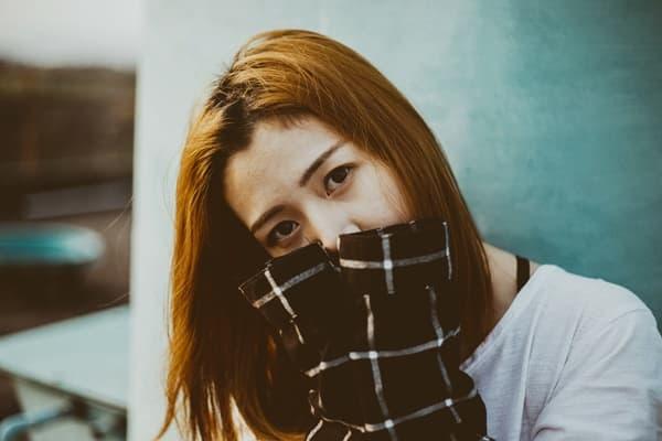 萌え袖で口元を隠し気持ちを察してもらいたがっている女性の画像