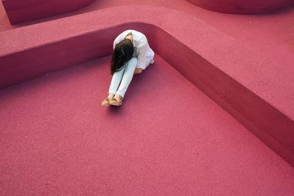 赤い床の上で膝を抱えて悩む女性の画像