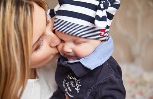 赤ちゃんにキスする女性の画像