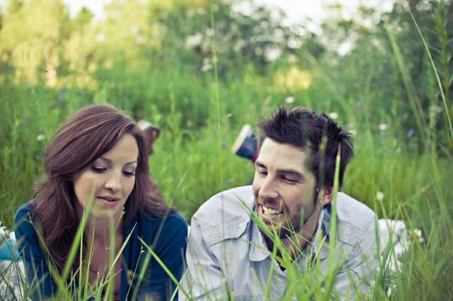 芝生で横になりながら話す夫婦の画像
