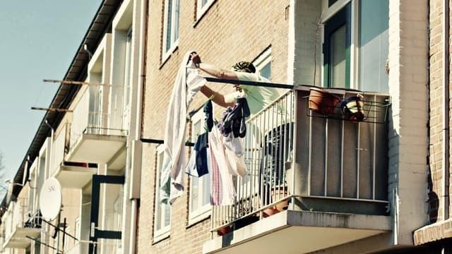 夫が洗濯物を取り込んで家事分担している画像