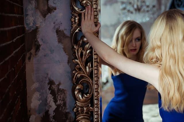 鏡に映る自分をブスだと思い悩み込む女性の画像