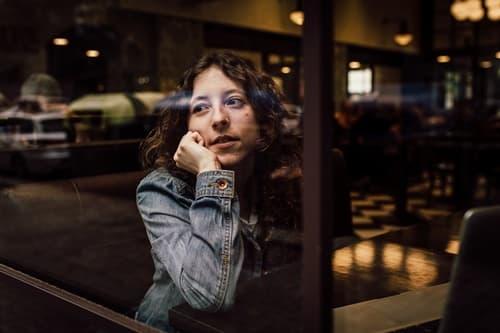 窓の外を見て待つ女性の画像