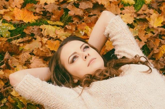 落ち葉の上で金銭感覚が合わない彼と交際を続けるか迷う女性の画像