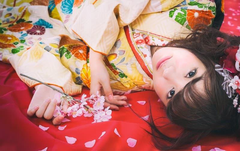 お正月に着物を着て寝そべる女性の画像