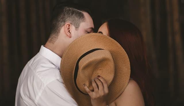 帽子で隠してヤリチンの友達とキスをする女性の画像