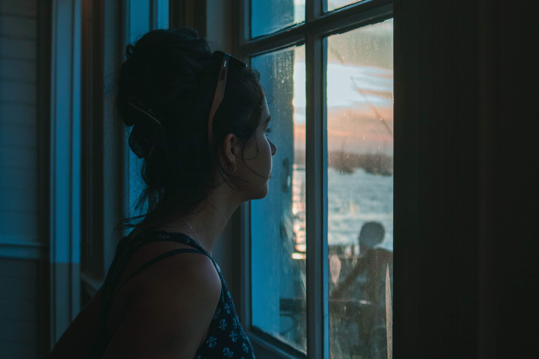 外を眺める女性の画像