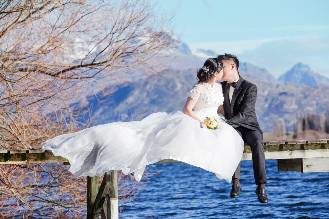海でキスをするウェディングドレス姿のカップルの画像