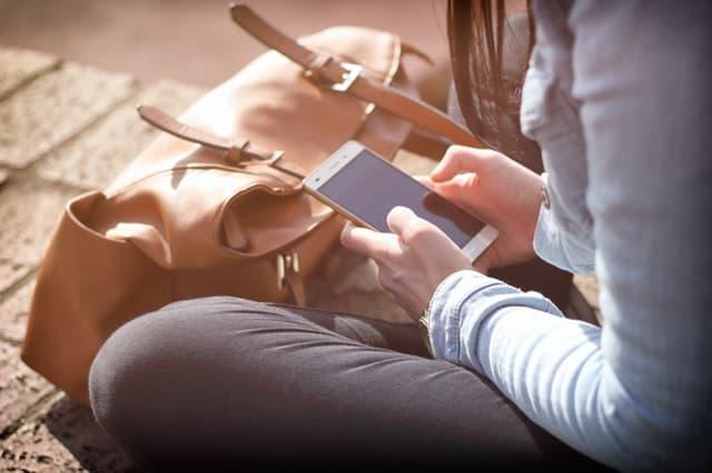 携帯電話を眺める女性の画像