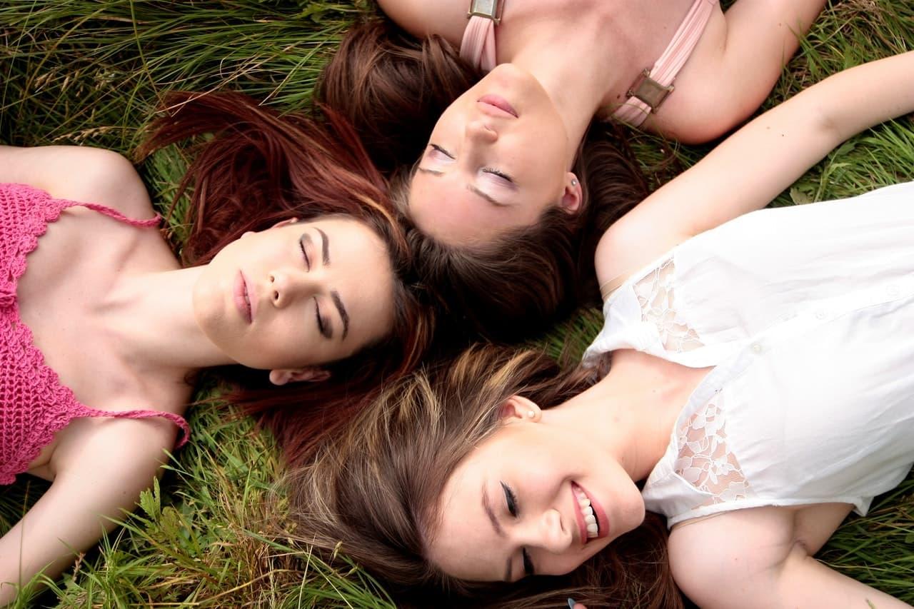 女子3人が芝生の上で寝転がっている画像