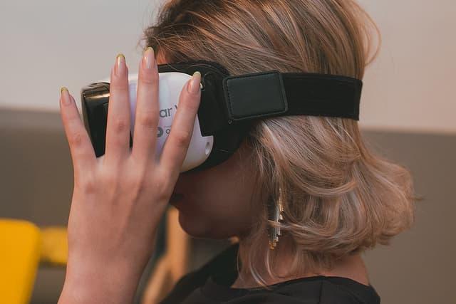 VR(ヴァーチャル・リアリティ)ゴーグルを装着する女性の画像
