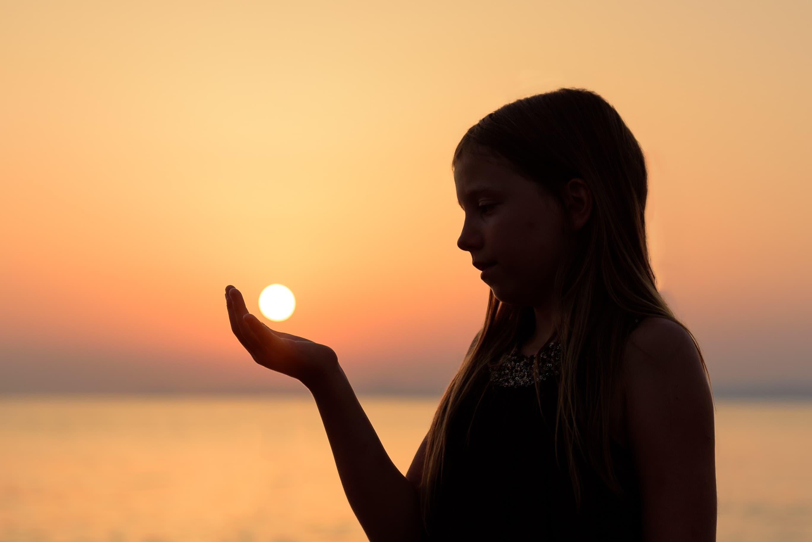 夕焼けをバックに一人で佇む少女の画像
