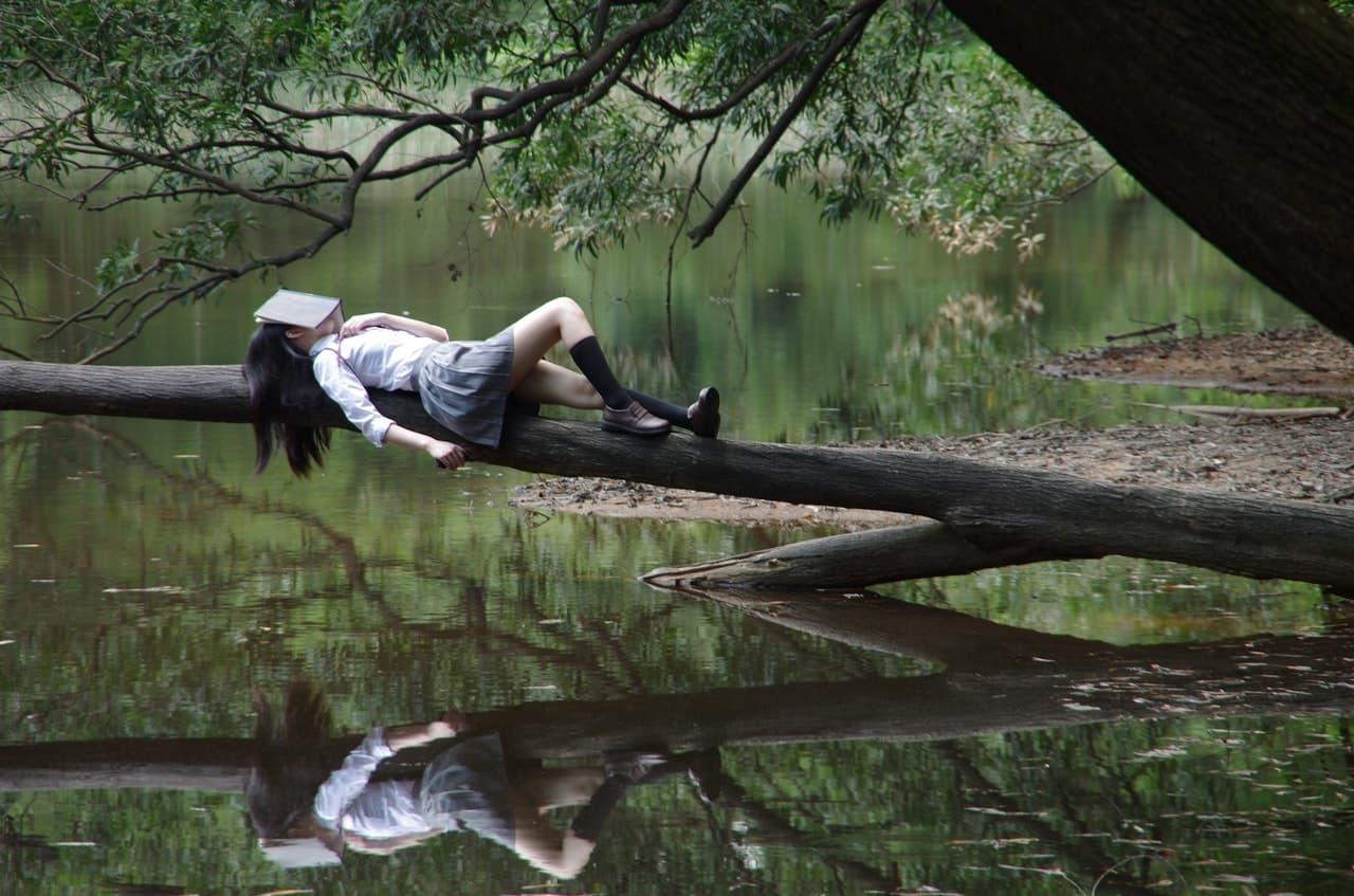 制服を着た少女が顔に本を乗せ湖で休んでいる画像
