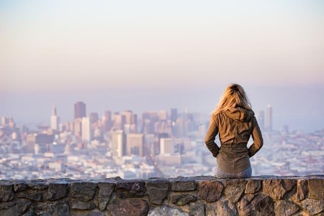 女性が腰掛けて都会の景色を眺める画像