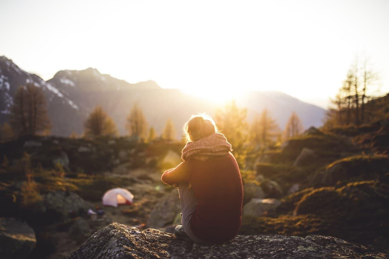 山でひとり朝焼けをみつめる女性の画像