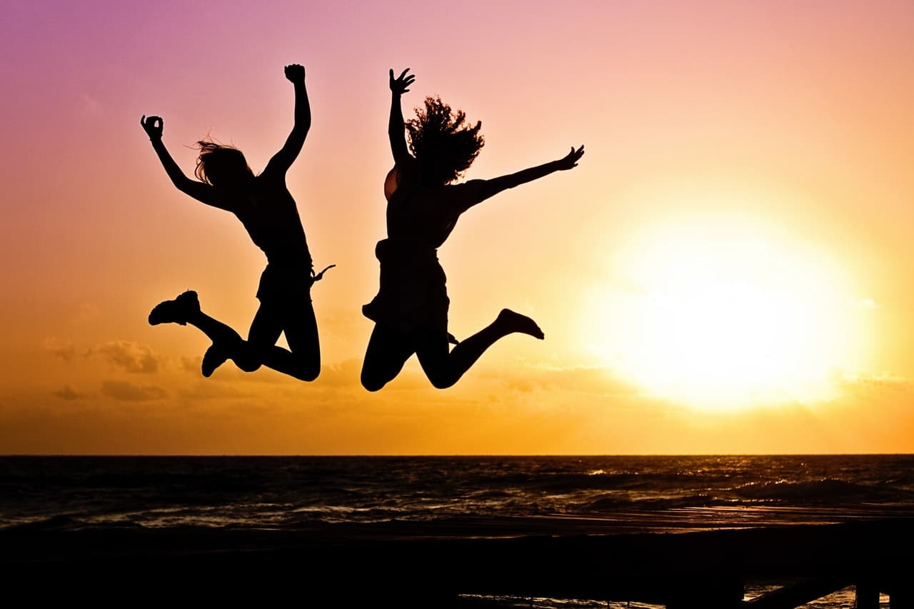 海辺でジャンプをする若い二人