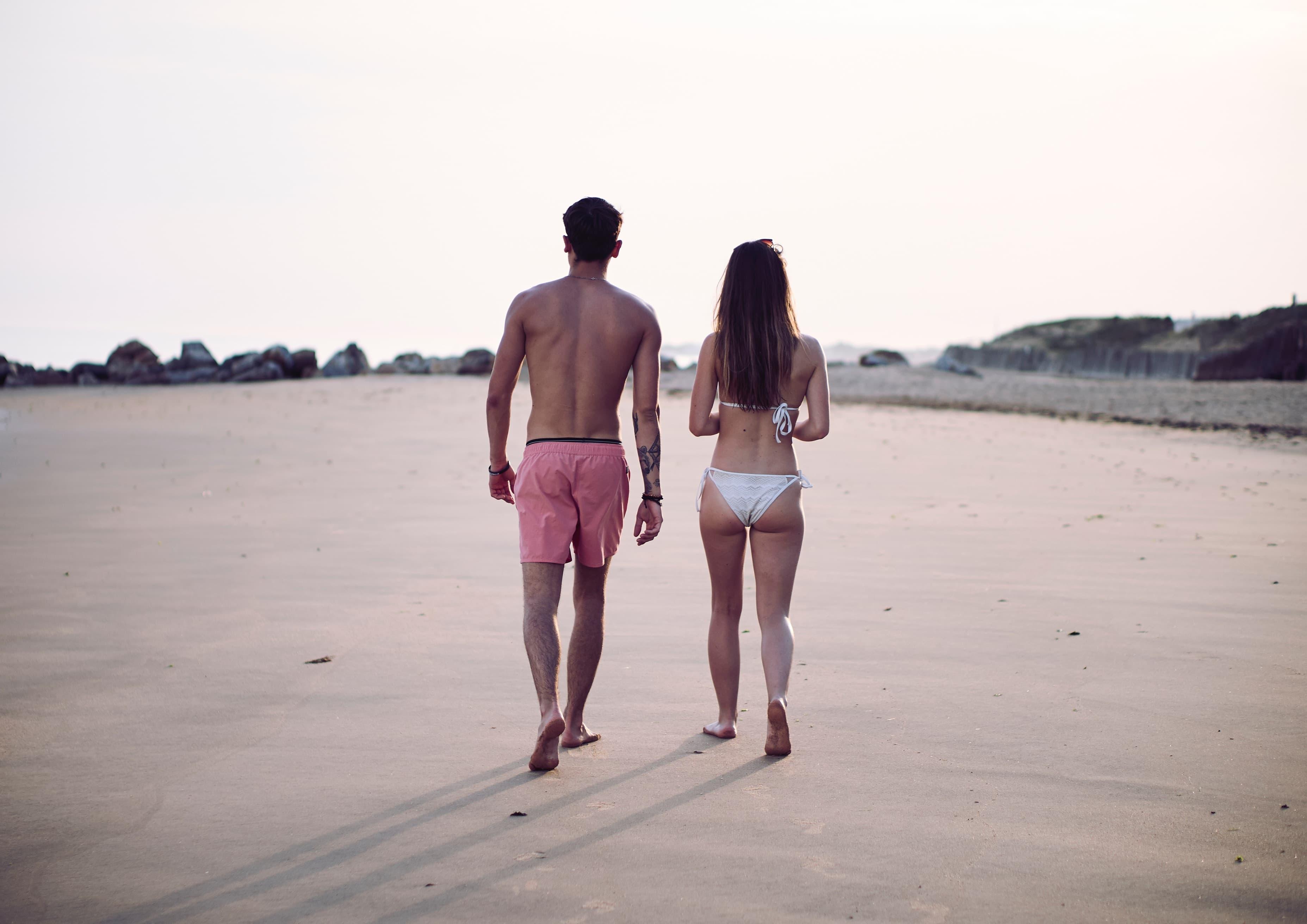 水着でビーチを歩く男女カップルの画像
