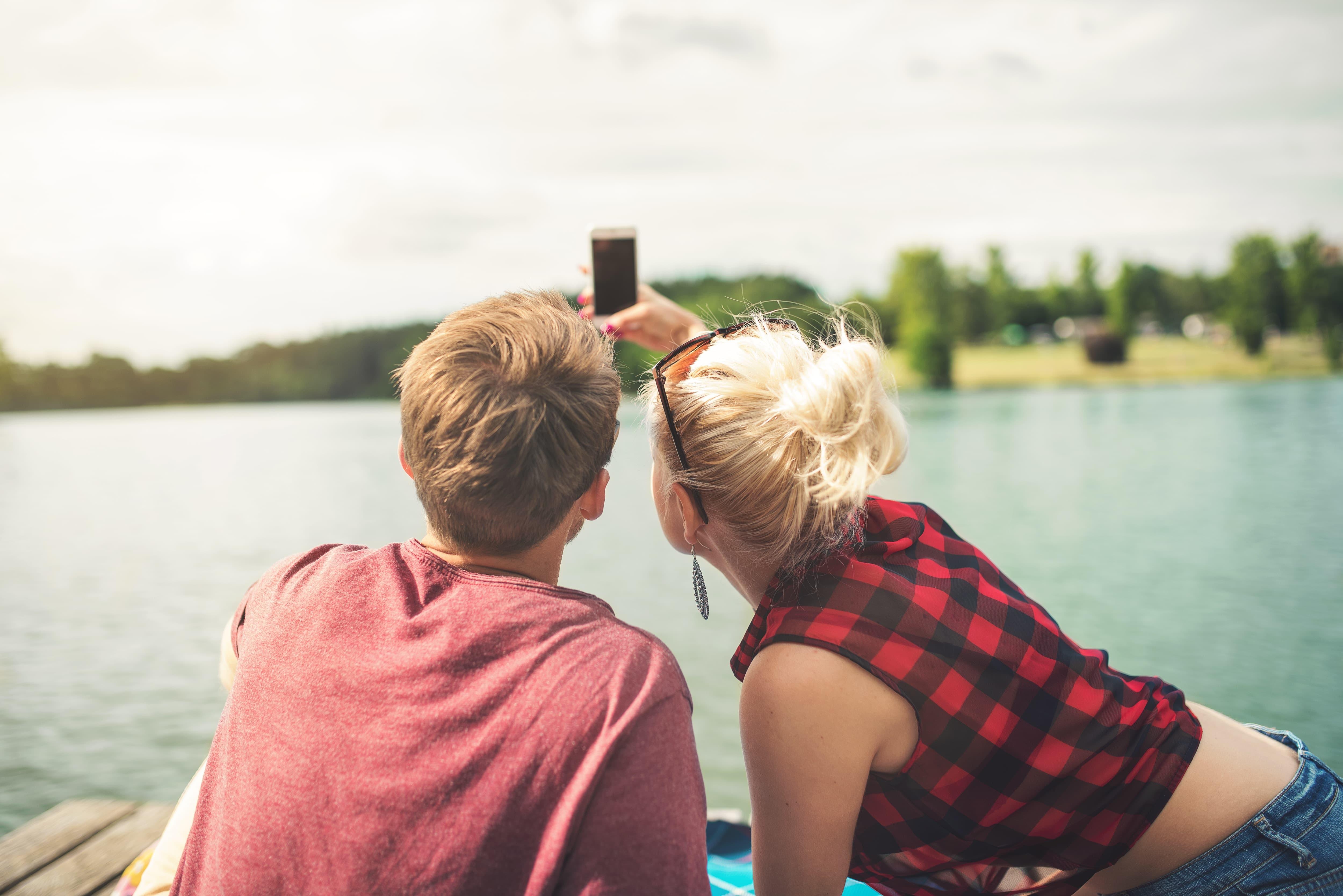 水辺で自撮りをするカップルの画像