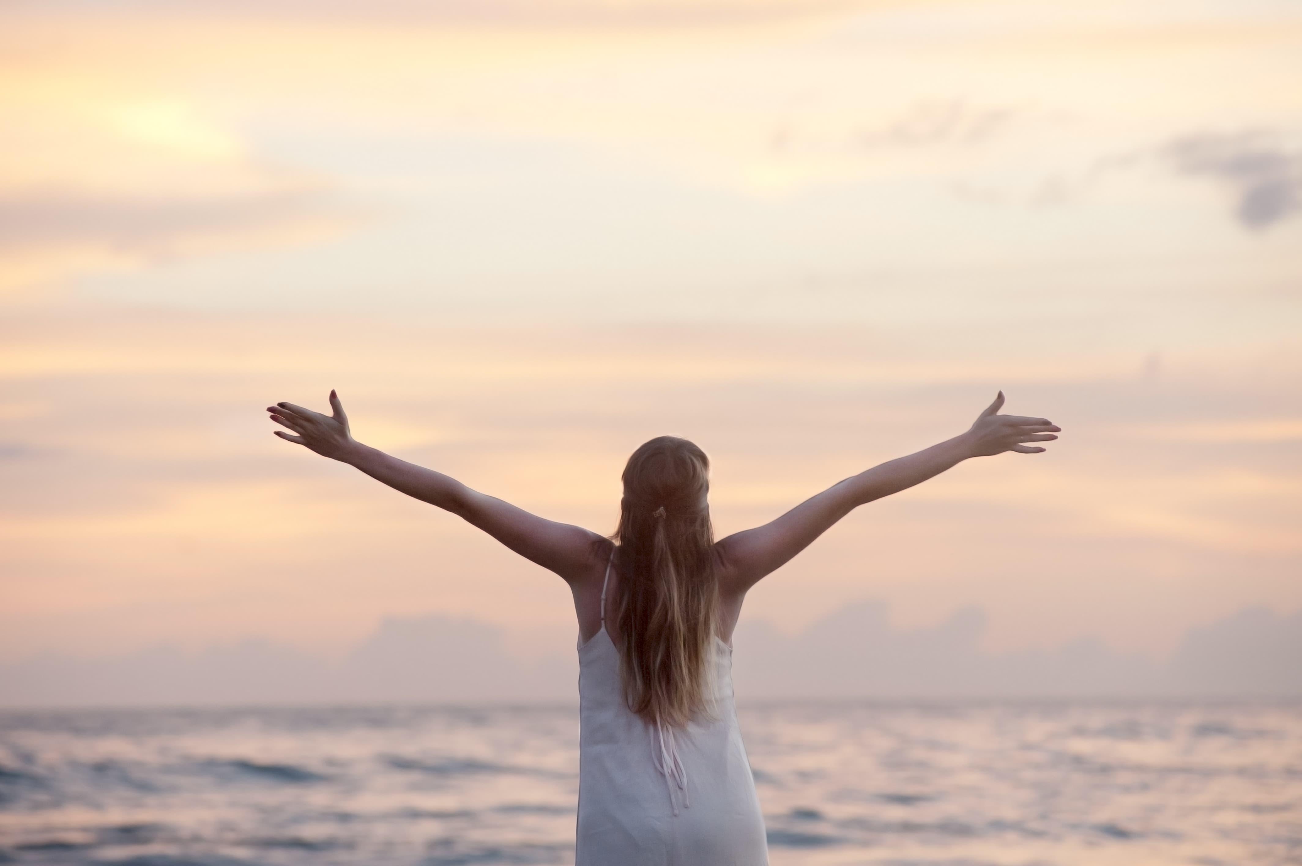 海に向かって両腕を広げる健康的な女性のサムネイル画像