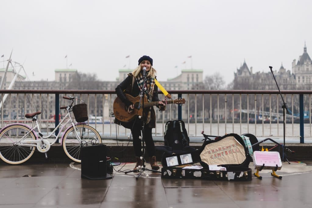 路上で歌うシンガーソングライターの女性の画像