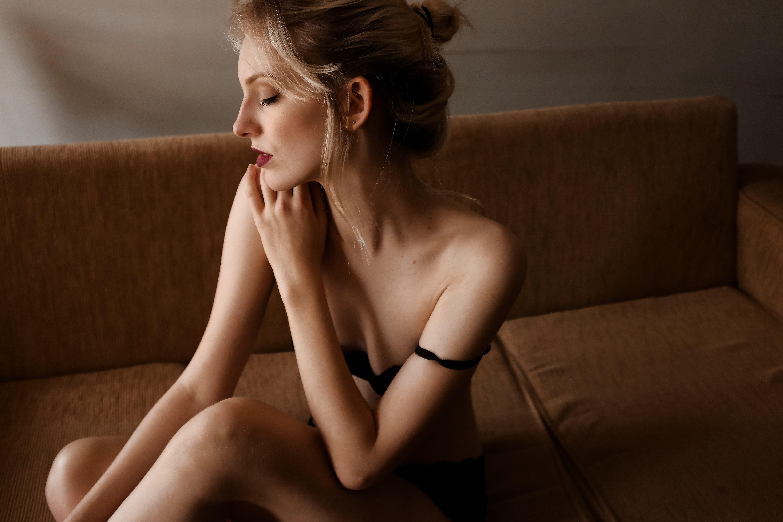 ソファでサティスファイヤを使っている美人な裸の女性の画像