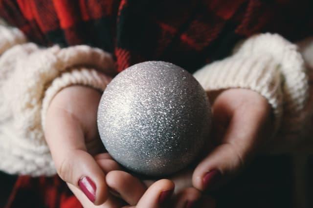 クリスマスのオーナメントのボールを手に持つ女性の画像