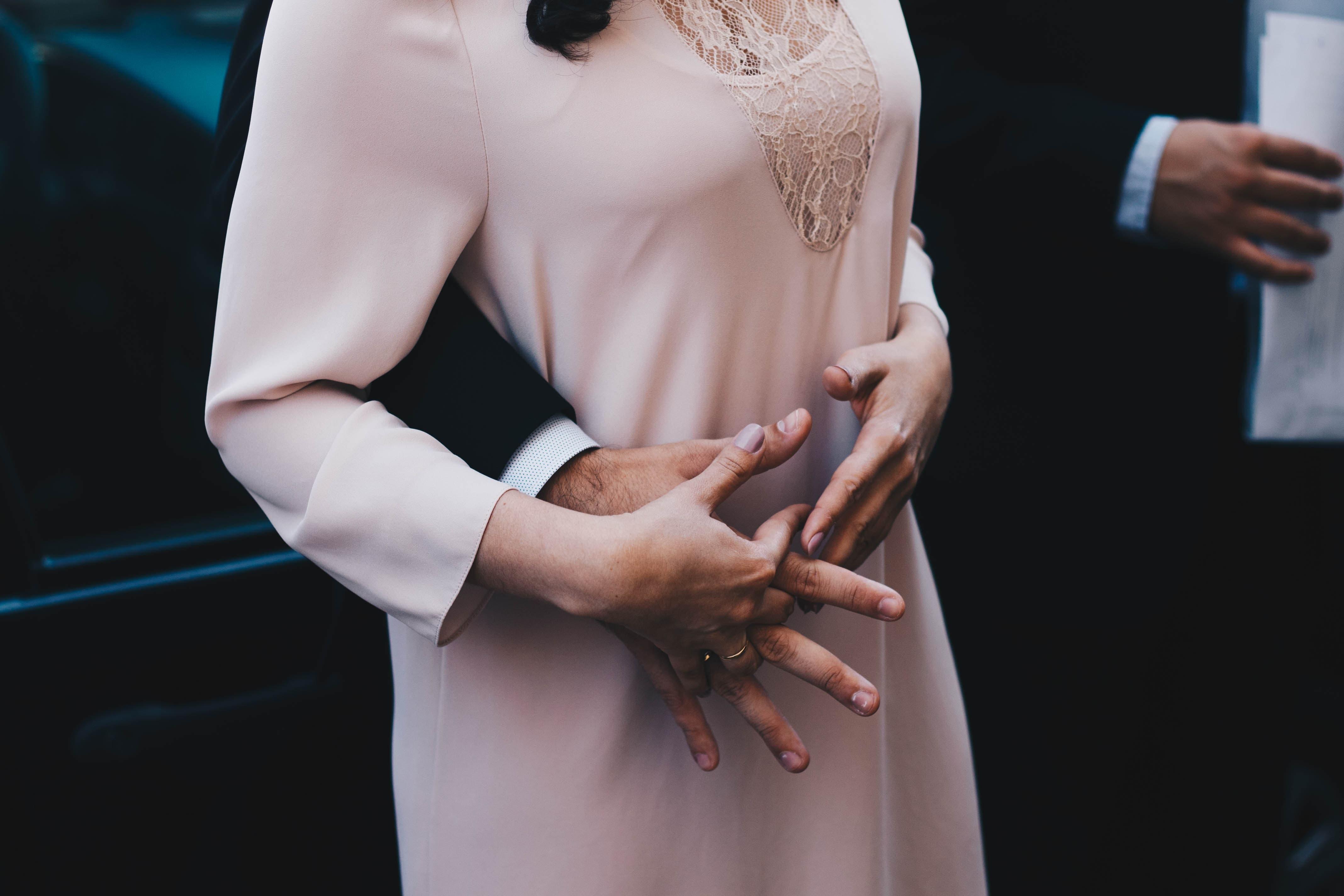 腹部に伸びる男性の手を上から握る女性の画像