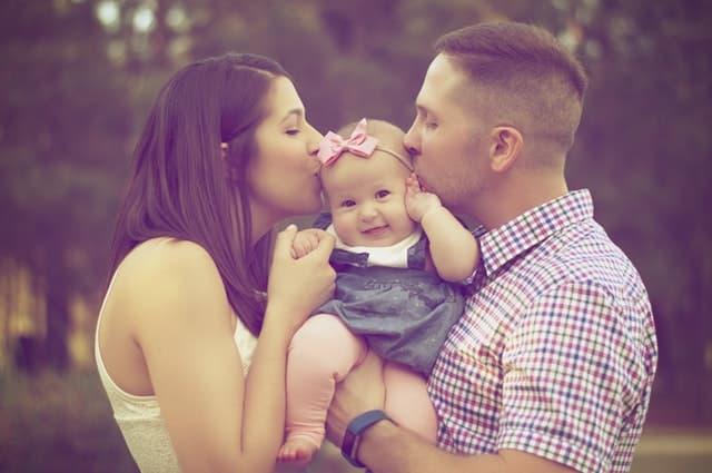 父親と母親がリボンをつけたわが子に口づけるサムネイル画像
