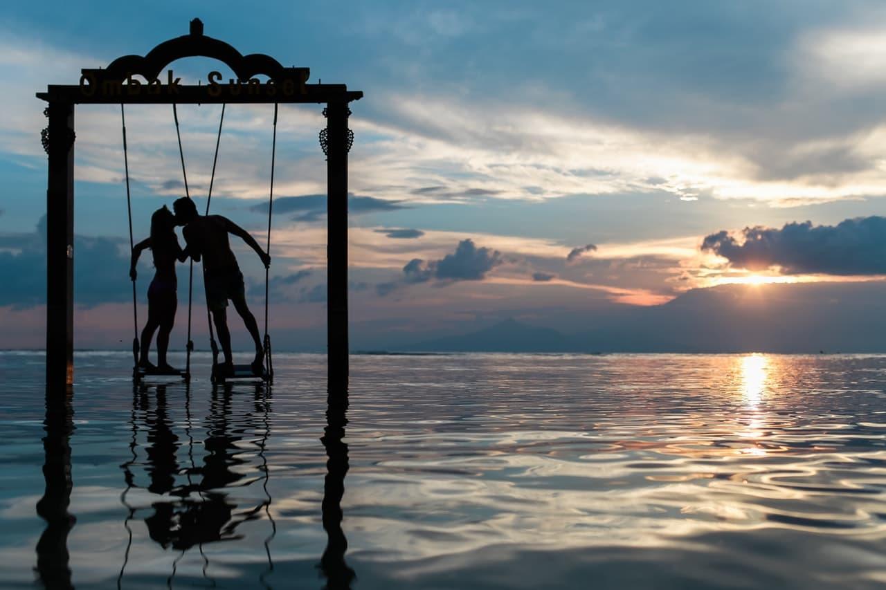 海辺のブランコでキスをするカップルの写真