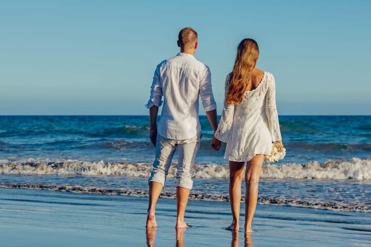 海に向かって歩む手をつないだカップルの画像