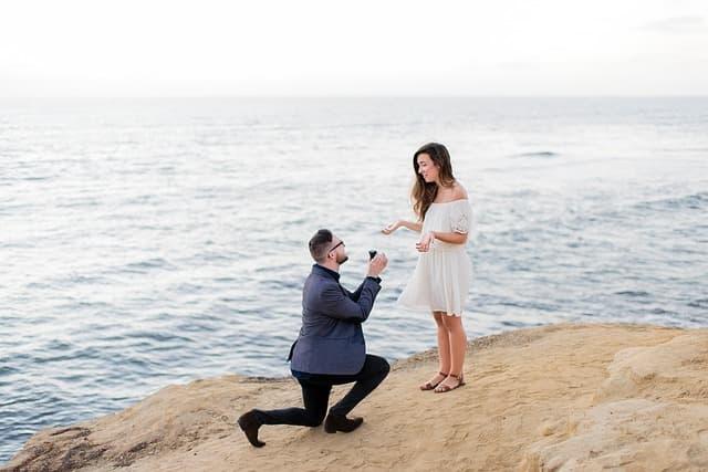 海辺で男性がモテる女性に告白・プロポーズしている画像