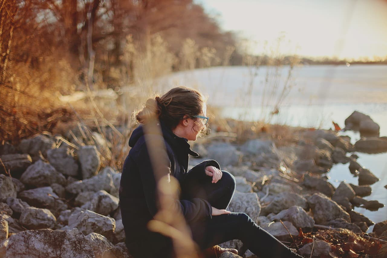 秋の夕暮れの湖畔でひとり佇む女性の画像