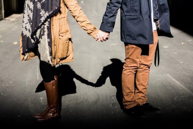 手をつなぎ違う方向を見る男女カップルの画像