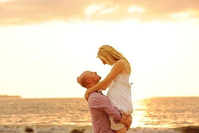 海辺で彼女を持ち上げる男性のロマンティックな画像