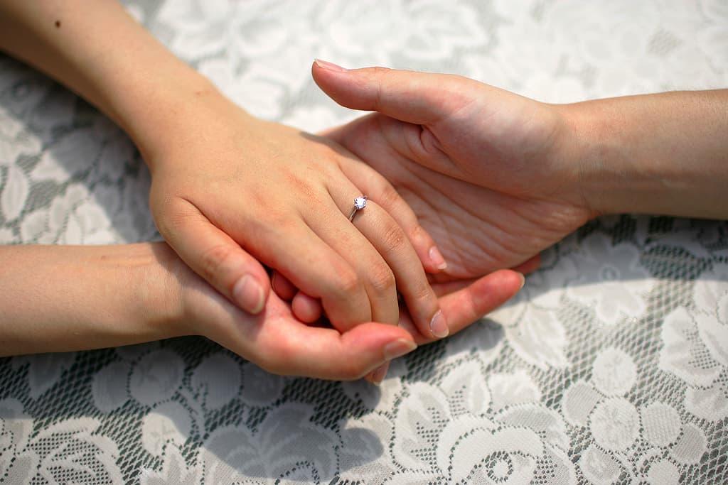 指輪をつけた男女が手を握り合う画像