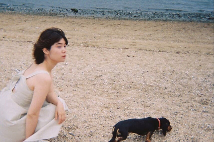 海辺で犬と写真に映る葭本未織さん